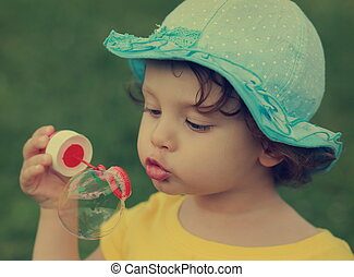 Cute child blowing big bubble Closeup vintage portrait