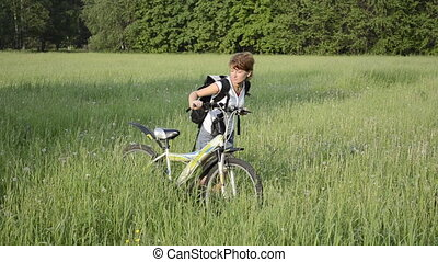 young woman with a bike is on the grass in the summer field