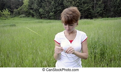 Happy young woman in summer field and mosquitoes