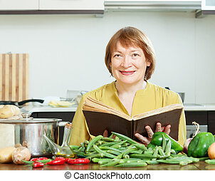 mature woman cooking with cookery book - mature woman...
