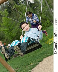 Baby boy playing on swing - Cute baby boy playing on swing...