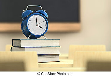 School time - Alarm clock over a pile of books in a...