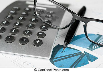 Pen, calculator and glasses on a background of diagrams