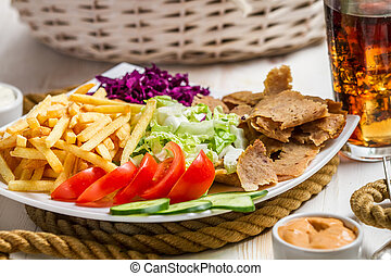 Closeup of vegetables, fries and meat kebab served with cold...