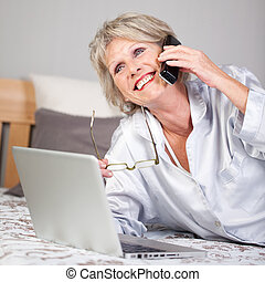 Woman With Laptop Using Cordless Phone In Bed - Happy senior...