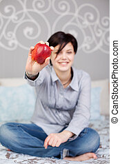 Woman Holding An Apple While Sitting In Bed - Full length of...