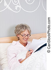 Happy Senior Woman Reading Book In Bed