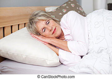 Senior Woman Sleeping In Bed - Senior woman smiling while...