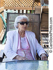 83 years old woman with sunglasses on chair outdoor