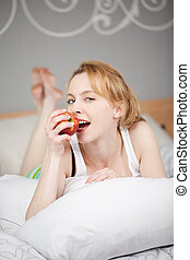 Young Woman Eating Apple While Lying On Bed