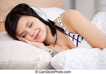 Listening music - Smiling woman lying on bed and feel the...