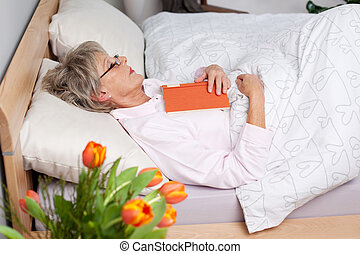 Senior woman fall asleep while reading a book in bed