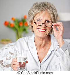 Senior Woman Holding Glass Of Water In Bedroom