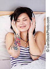 Woman Listening To Music On Headset While Lying In Bed -...