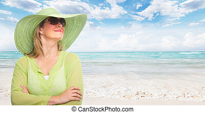 Senior woman wearing sunglasses and a hat.