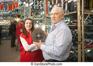 mature man and woman in auto parts store - mature man and...