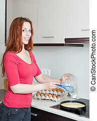 Smiling woman making scrambled eggs in frying pan at home