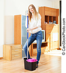 Cheeful ordinary woman washing parquet  with mop in home