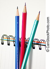 Three pencil on the notebook white background