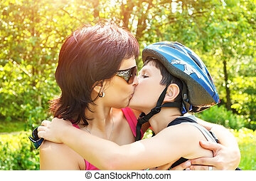 Mother kisses her son outdoor
