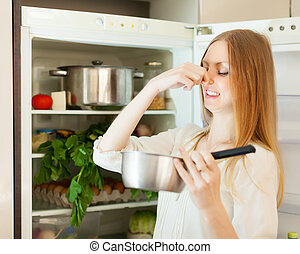 Long-haired woman holding foul food - Long-haired woman...