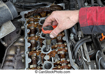 Automotive ignition coil - Car mechanic replacing ignition...