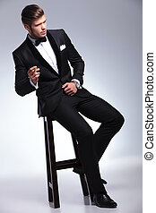 business man looks away while smoking on chair - elegant...