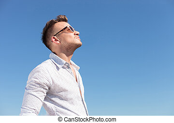 casual man looking at the sun - casual young man outdoor...