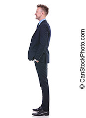 business man stands sideways and smiles - full length side...