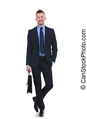 business man stands with suitcase and hand in pocket - full...