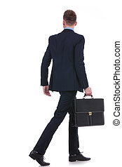 back of a business man with suitcase walking away - full...