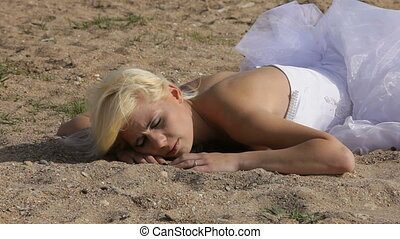 Bride on a beach - Bride laying on the sand while someone...