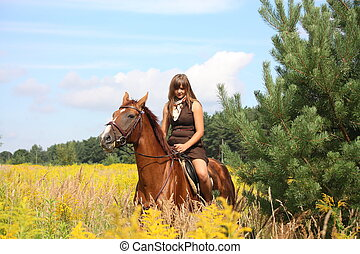 Beautiful teenager girl riding horse at the field of flowers...