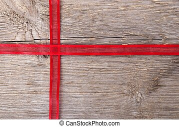 red ribbon as gift - red ribbon on wood in shape of a cross...