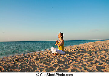 Yoga on the beach at sunrise - Woman doing yoga on the beach...