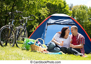 Happy couple on a camping drinking prosecco - Happy young...