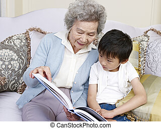 grandma and grandson reading a book together.