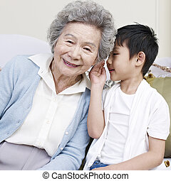 grandma and grandson - grandson telling grandma a secret.