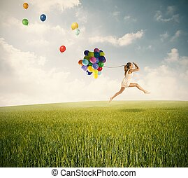 Jumping with balloons in a green field