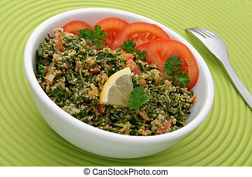 Tabbouleh with tomato slices in a white bowl, ready to eat