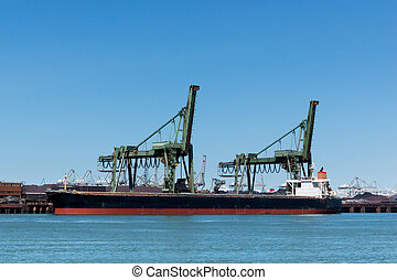 Ship is unloading the iron ore - Large vessel unloading its...