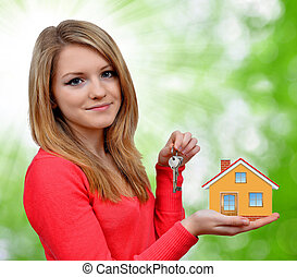 girl holding in hands house - girl holding in her hands a...