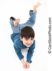 Happy Boy - Adorable five year old boy laying barefoot on a...