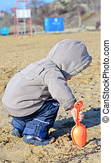 Young boy playing on the beach sand with a small orange...