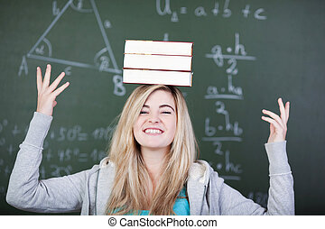 Student balancing three books on her head