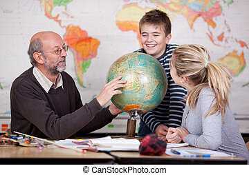 Teacher explain about globe to his students - A young male...