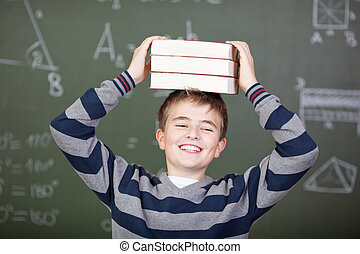 Male Student Carrying Stacked Books On Head Against...