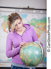 Schoolgirl pointing a place on a globe - Teenage schoolgirl...