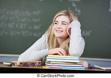 Student Looking Away At Desk In Classroom