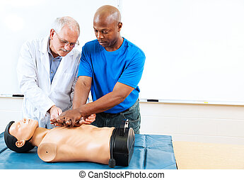 Adult Education - First Aid Training - Doctor teaching first...
